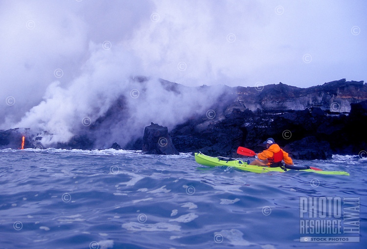 EDITORIAL ONLY. Kayaking near Kilauea volcano lava flow as it enters the Pacific Ocean
