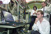 Seated at a simulated ISS workstation, Soyuz 5 Nominated Space Flight Participant Lance Bass, a member of the pop singing group 'N Sync, listens to instructions from a briefer (out of frame) as part of a training and familiarization tour on August 26, 2002 at the Lyndon B. Johnson Space Center in Houston, Texas. Standing behind Bass are Ginger Kerrick of JSC's International Training group and Herve Stevenin of the European Space Agency. .Credit: NASA via CNP
