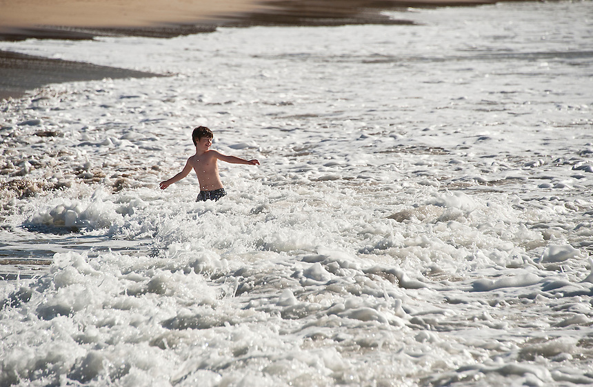 Boy swimming in ocean surf.