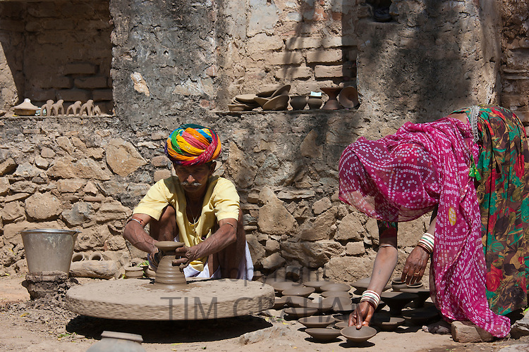 Indian potter in Rajasthani turban works at home with his wife making clay pots in village of Nimaj, Rajasthan, India