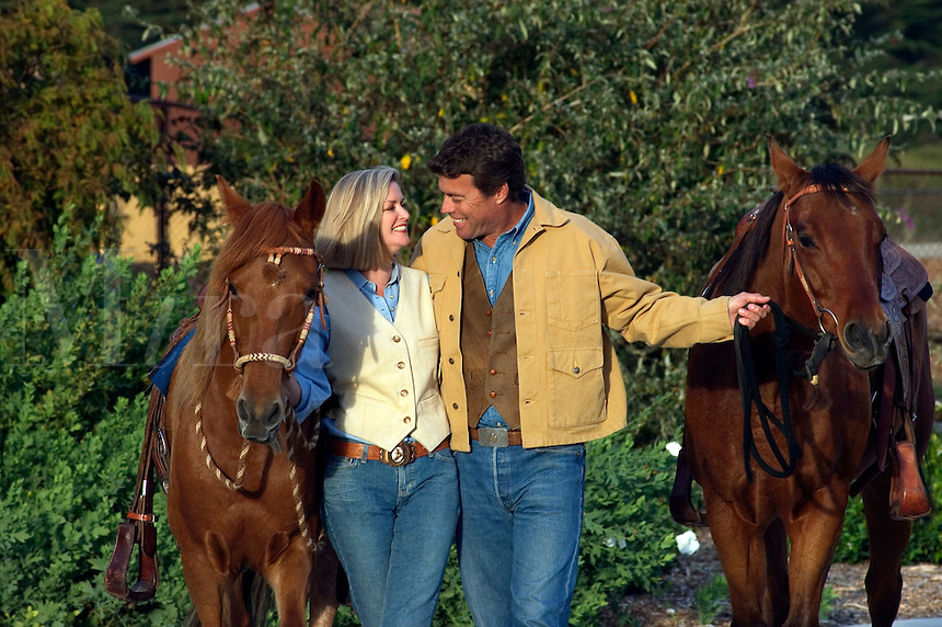A cowboy couple walk their horses after a a romantic ride