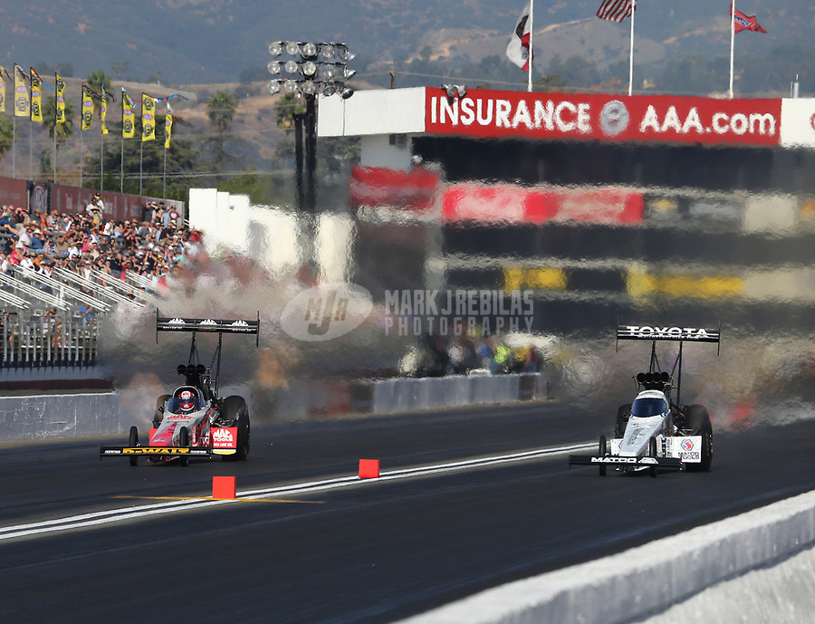 Feb 9, 2018; Pomona, CA, USA; NHRA top fuel driver Doug Kalitta (left) against Antron Brown during qualifying for the Winternationals at Auto Club Raceway at Pomona. Mandatory Credit: Mark J. Rebilas-USA TODAY Sports