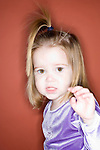 three year old girl posing in front of the camera with her hair up in a purple shirt with a red background