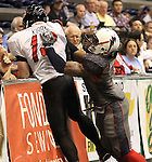SIOUX FALLS, SD - MAY 18:  Quarterback Cody Kirby #13 from the Chicago Slaughter is pushed out of bounds by Tyler Knight #3 from the Sioux Falls Storm in the first half of their game Saturday night at the Sioux Falls Arena.  (Photo by Dave Eggen/Inertia)