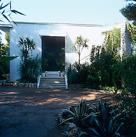 The exterior of the 1970's house on the Cote d'Azur with flowerbeds filled with aloe and bamboo