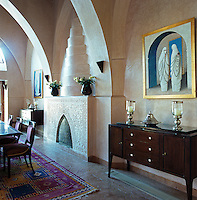 A pair of Modernist sideboards with candle holders and silver tagine platters flank the fireplace in the dining room