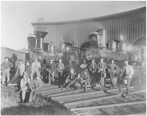 With brass bells and whistles gleaming, two T-12 class locomotives serve as striking props for this photo taken at the Chama turntable. Trainmen of various roles, many with tools such as the long locomotive oil can, pose with the iron beasts, making clear the connection between man and machine found on railroads everywhere. The locomotives are #166 and #16?<br /> D&amp;RG  Chama, NM