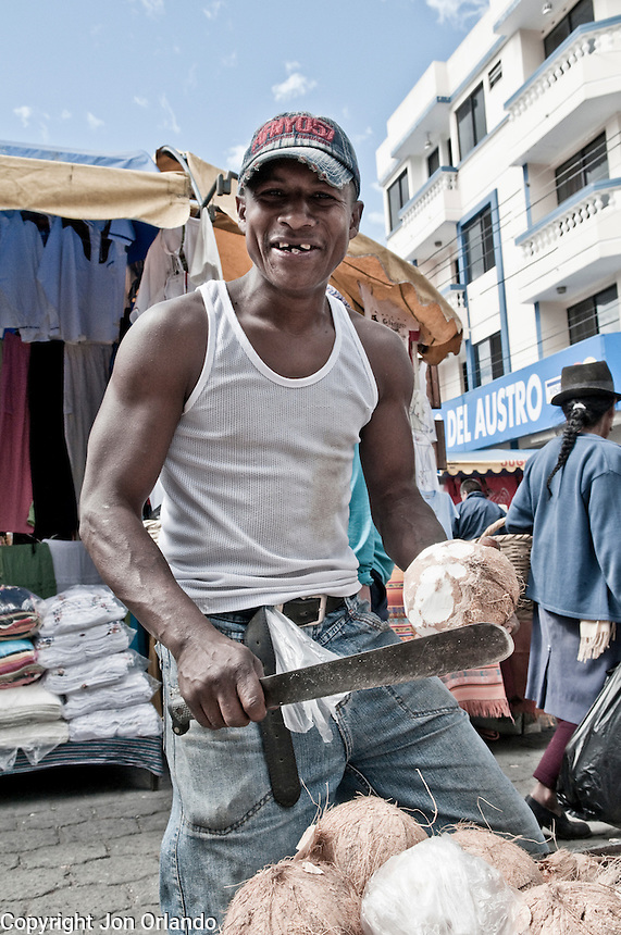 A man selling Coconuts at the indigenous market in Otavalo, Ecuador.