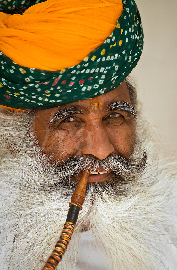A turbaned Rajasthani man demonstrates the use of a HOOKAH PIPE in the MEHERANGARH FORT - JOHDPUR, RAJASTHAN, INDIA