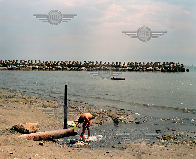 Boy playing in the water at an outflow pipe near a concrete pier surrounded by riprap, which prevents erosion of the beach.  Venus is one of a string of holiday resorts on the Romanian Black Sea Riviera named after planets.