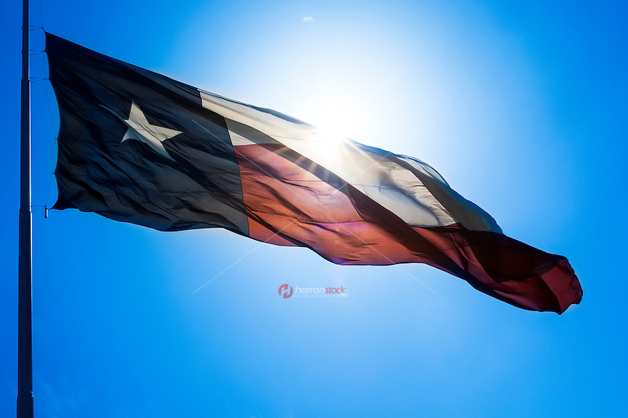Texas state flag with sun flare waving in the wind of bright blue