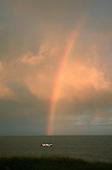Natal, Brazil. Rainbow off Ponta do Seixas, the most easterly point of Brazil; speedboat at the end of the rainbow.