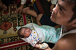 6 January 2020, Cipinas Village, Lebak Regency, Banten Province, Indonesia: 32 year old Jamaludin with his newborn baby, Sita Mustafa, who was born in an emergency shelter in Cipinas sub district, Lebak regency, Banten Province. After his wife Ibu Ana fled her flood ravaged village of Cinyiru she walked many kilometres in the rain along collapsed roads and landslides before she gave birth to her baby. The flooding in and around Jakarta in recent days has killed 66 people and forced hundreds of thousands to flee with many losing everything from landslides and floods. Picture by Graham Crouch/The Australian