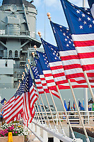 A row of American flags lead to the battleship USS Missouri museum in Pearl Harbor, O'ahu.