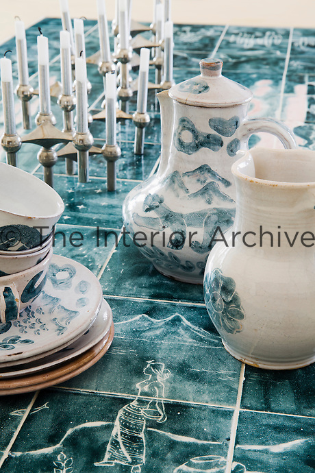 The dining table top has an section inlaid with vintage blue ceramic tiles, which are complemented by the blue and white tea pot and cups and saucers.