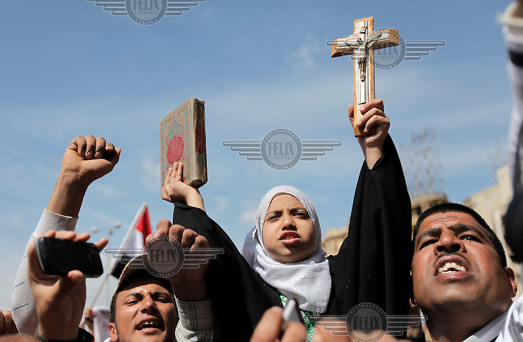 A girl holding a cross and a Qur'an. Christians and Muslims came together on Friday prayers in Tahrir square, advocating peaceful co existence. Sectarian violence had flared in the wake of the revolution that saw president Hosni Mubarak removed from office.