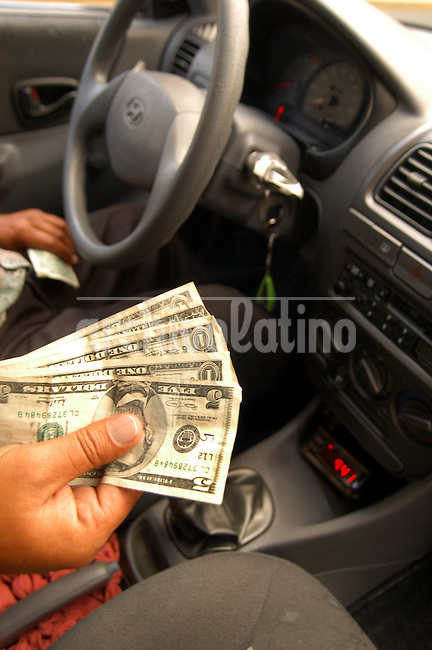 "Un taxista da el vuelto en dolares a un cliente que acaba de pagar por sus servicios. Desde el año 2000 Ecuador dolarizó su economía y todas las transacciones se realizan en dolares americanos.+ economia *A taxi driver gives change in US dollars . From  year 2,000 Ecuador dolarized its economy and all the transactions are carried out in American dollars. *Un taxi rend la monnaie à un client en dollars américains. Depuis l'an 2000, l'Equateur à ""dollariser"" son économie, et donc toutes les transactions sont effectuées en dollars américains. +politique, monnaie, dévaluation, économie, commerce, pétrole........"