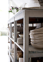 A collection of rustic crockery is displayed on open shelving under a kitchen worktop