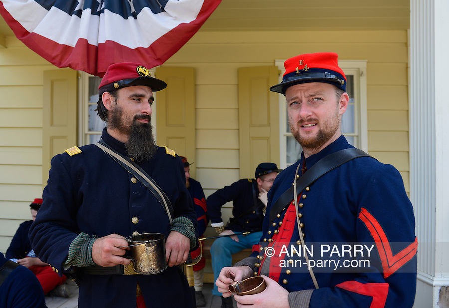 """Old Bethpage, New York, USA. August 30, 2015. L-R at front, ANDREW PREBLE from Long Beach, and MATT DELLINGER from Brooklyn, portray American Civil War soldiers from the 14th Brooklyn Regiment (14th New York State Militia) AKA The Brooklyn Chasseurs, at the Noon Inn tavern during the Old Time Music Weekend at the Old Bethpage Village Restoration. During their historical reenactments, members of the non-profit 14th Brooklyn Company E wear accurate reproductions of """"The """"Red Legged Devils"""" original Union army uniform."""