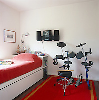 A simple boy's bedroom dominated by a contemporary drum kit