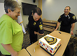 (Watertown 042013) Lt. James O'Connor, center, compares his patch on his arm patch to the one the cake brought into the Watertown Police Department by Beth Sehakian, left, of Watertown, made by her daughter Jessa, a professional baker, as officer Ken Swift looks on. (Jim Michaud Photo) For Sunday