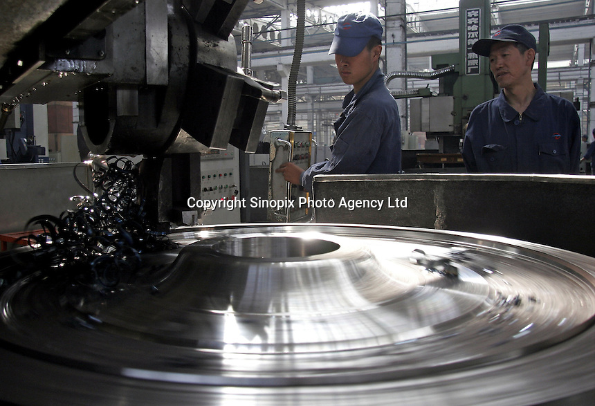 A Chinese worker operates a machine that fabricates locomotive wheels at the state-owned Datong Electric Locomotive Co. LTD in Datong, Shanxi Province, China. China's developing economy has created a huge demand for faster and more powerful locomotive engines to move its people and goods within its vast and expanding railway network, the Datong company is currently working together with several western partners including Alstom of France and ABC of the U.S..05 Jul 2005