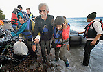 Refugees land on a beach near Molyvos, on the Greek island of Lesbos, on October 31, 2015. Part of a boatful of refugees that arrived from Turkey, they were received by local and international volunteers, then proceeded on their way toward western Europe. The boat was provided by Turkish traffickers to whom the refugees paid huge sums to arrive in Greece.