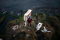 A fisherman with a makeshift Styrofoam raft brings his catch and raft ashore in Havana, Cuba on 9 October 2008.