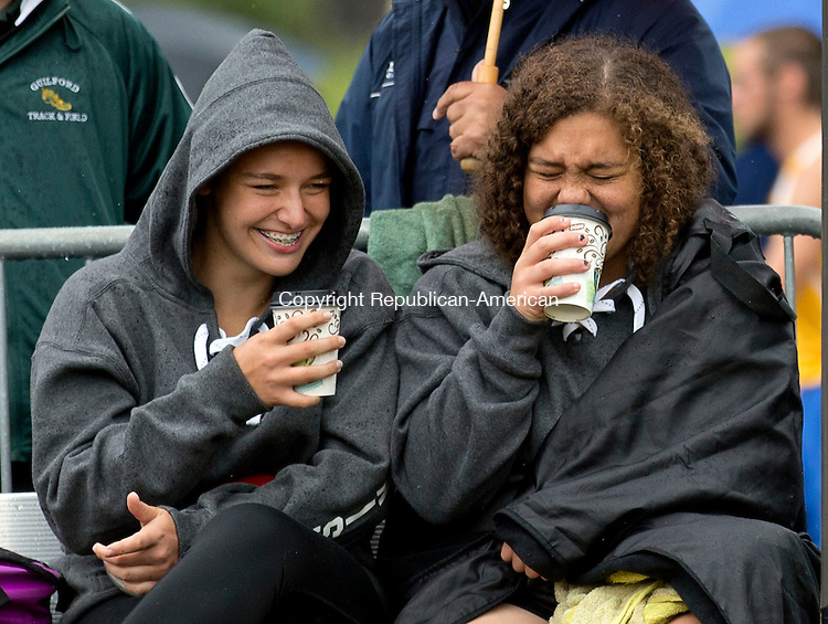 Middletown, CT- 02 June 2015-060215CM01- Torrington's Caitlyn Cornish, left,  and Kendra Covington share a laugh as they try and keep warm before the discus event during the Class MM Track and Field Championships at Middletown High School on Tuesday.    Christopher Massa Republican-American