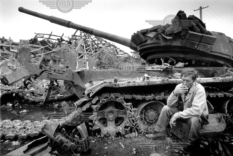 "©Heidi Bradner/Panos Pictures..Chechnya. Vika, A Russian man who was born in Grozny, sits near a destroyed tank in central Grozny ""to remember the crew that died inside,"" he said. The number of ethnic Russians in Grozny has dramatically decreased since the start of the first war."