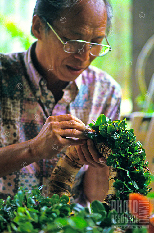 Man working on making a wreath at the Lyon Arboretum in Manoa Valley