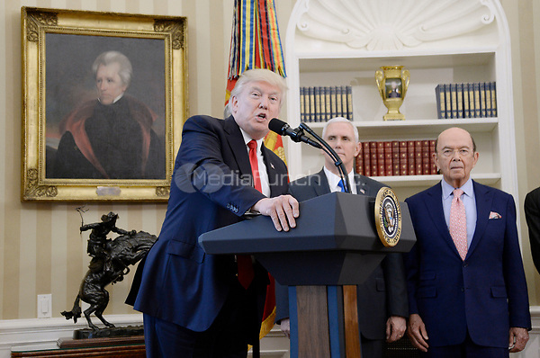 United States President Donald Trump speaks about trade as US Vice President Mike Pence and US Secretary of Commerce Wilbur Ross look on before signing Executive Orders  in the Oval Office of the White House March 31, 2017 in Washington, DC. <br /> Credit: Olivier Douliery / Pool via CNP /MediaPunch