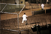 Guantanamo detainees wake up before dawn and play football before the morning prayer inside Camp Delta at the American naval base at Guantanamo Bay, where over 600 alleged al Qaeda members have been held indefinitely. Described by the US as 'unlawful enemy combatants', they were captured primarily in Afghanistan during the 'war against terror'.