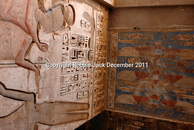 """Wall and ceiling between the First Court and the  Second Court at the mortuary temple of Ramses III at Medinet Habu at Thebes.Thebes was the ancient capital of Egypt and was built in and around modern day Luxor.The ancient name for Medinet Habu was Djamet meaning """"males and mothers."""" Its holy ground was believed to be where the Ogdoad,the four pairs of primeval gods,were buried.Medinet Habu was both a temple and a complex of temples.Queen Hatshepsut who ruled Egypt from 1479-1458 BC  and Tuthmosis III who reigned from 1479-1425 BC built a small temple to Amun on the site of an earlier structure. Next to their temple, Ramses III who reigned from 1186-1155 BC built his mortuary temple.He then enclosed both structures within a massive mud-brick enclosure.The temple precinct measures about 700 feet by 1000 feet and contains more than 75,350 sq ft of decorated surfaces across its walls.It is the best preserved of all the mortuary temples of Thebes."""