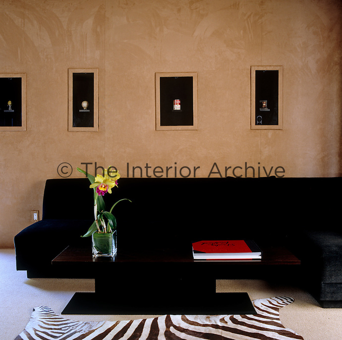 Niches in the cinema room's beige suede walls display a series of 'precious' objects