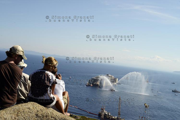 Roma, 23 Luglio 2014<br /> Isola del Giglio<br /> Operazione di rimozione della nave da crociera Costa Concordia, naufragata il 13 Gennaio del 2012.<br /> La nave lascia l'isola.<br /> Una barca spruzza acqua sulla Concordia per buon augurio.<br /> <br />  Concordia Wreck Removal Project, Giglio Island<br /> The Concordia has gegun its navigationtowards Genoa.