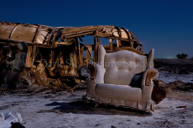 A tattered easy chair and ruined trailer house sit in the salt encrusted mud of a flooded neighborhood in Bombay Beach, California on the shore of the Salton Sea