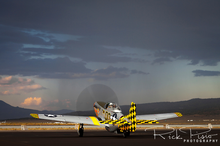 P-51 Mustang and passing rain squall on the ramp at Stead Field in Nevada