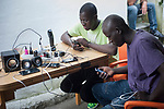 Two African migrants attend their smartphones in Lakaxita. Irun (Basque Country). August 30, 2018. Lakaxita is a self-managed socio-cultural space located in an occupied house, where volunteers have created a hosting network for migrants in transit who have already completed the 5-day period that can remain in public resources. This group of volunteers is avoiding a serious humanitarian problem Irún, the Basque municipality on the border with Hendaye. As the number of migrants arriving on the coasts of southern Spain incresead, more and more migrants are heading north to the border city of Irun. (Gari Garaialde / Bostok Photo)