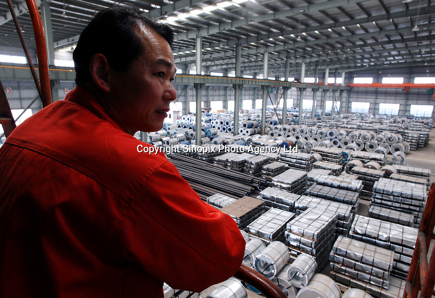 A crane operator looks onto a floor filled with steel products as he takes a break on a perch at a warehouse run by the Shanghai Yirong Trading Company Ltd in Shanghai, China..10 Apr 2009