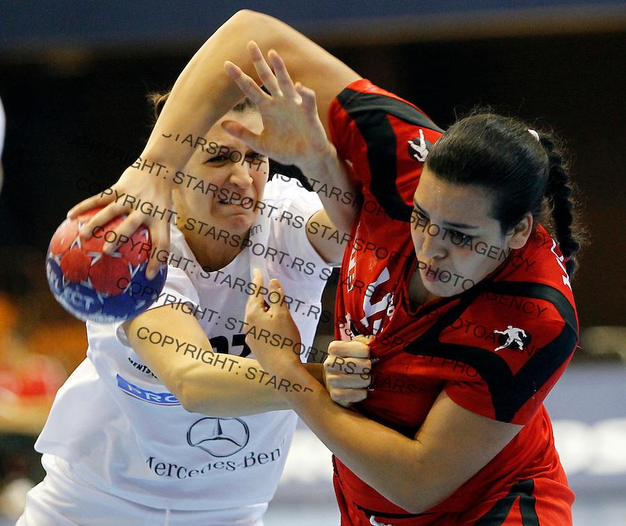Tunisia's Manel Kouki (R) vies with Hungaryís Klara Szekeres (L) during their Women's Handball World Championship 2013 match Tunisia vs Hungary on December 9, 2013 in Novi Sad.   AFP PHOTO / PEDJA MILOSAVLJEVIC