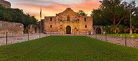 Alamo Sunrise Panorama - San Antonio landscape on prints, canvas and metal. We captured the Alamo in San Antonio at sunrise in a panorama with the early morning color in the sky over this historic landmark. The Alamo was originally known as Misi&oacute;n San Antonio de Valero and was founded as a Catholic mission in 18th century as a mission and fortress compound along with educational purpose for the American Indian. Today it is part of the San Antonio Missions National Historical Park and is a World Heritage Site. This historic landmark site is part of the San antonio cityscape which draws thousand of tourist year round to come to the mission and discover the historic significance of this place. The Alamo is treated with a lot of reverence so be respectful when inside at all times. Today it is part of San Antonio greatest toursit attraction because of it contribution to history. During the revolution a small number of Texians were at the compound when the Mexican Army attacked and kill most who were left inside and burned some of the place down. Many know the history of Battle of the Alamo as William Travis and his men like Daniel Boon and Jim Bowie fought Santa Anna Army. The Alamo was brought back to life when the Daughter of the Republic in 1835 started trying to preserve it and had maintained it until 2015 when the Texas Land Office took over the site. Today it is probably one of the most popular tourist spots in the state of Texas. People travel here to see these historic missions that San Antonio has so many of.<br /> <br /> Note: To see more of our mission please go to our Texas Mission Gallery.