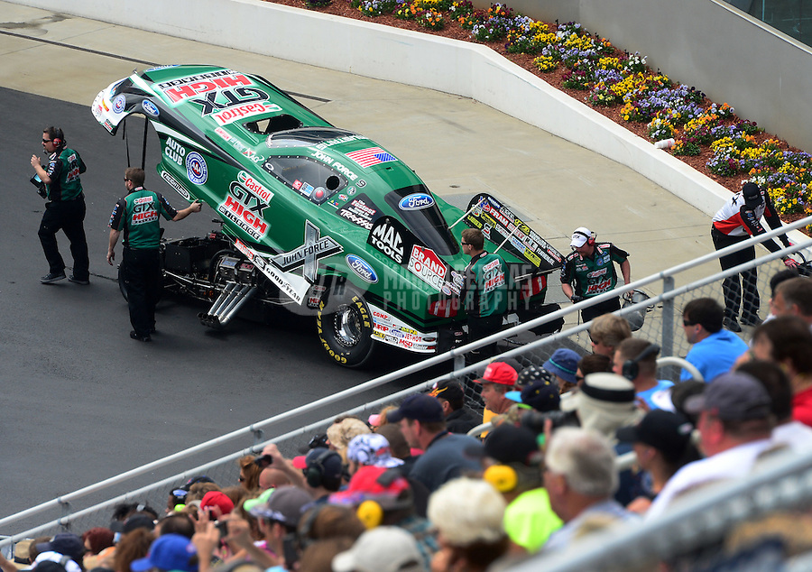 Apr. 15, 2012; Concord, NC, USA: Crew members push the car of NHRA funny car driver John Force during eliminations for the Four Wide Nationals at zMax Dragway. Mandatory Credit: Mark J. Rebilas-