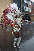 25/08/2014. London, England. Performers from the Paraiso School of Samba. Rain couldn't dampen the spirit of the Notting Hill Carnival performers on an extremely wet and miserable Bank Holiday Monday.  Many were soaked to the skin.