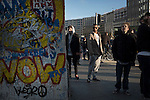 A group of young men looking at a section of the Berlin Wall on display outside Potsdamer Platz S-Bahn station. The route of the Wall, which stood from 1961-1989, has been developed into the 'Mauerweg,' a thoroughfare which traces most of the route of the Wall which encircled the city and divided it into East and West Berlin during the Cold War. In the years following the 1989 civil uprising in the German Democratic.Republic, most of the Wall was removed as part of the reunification strategy which united the pro-Soviet DDR and the Federal Republic of (West) Germany.