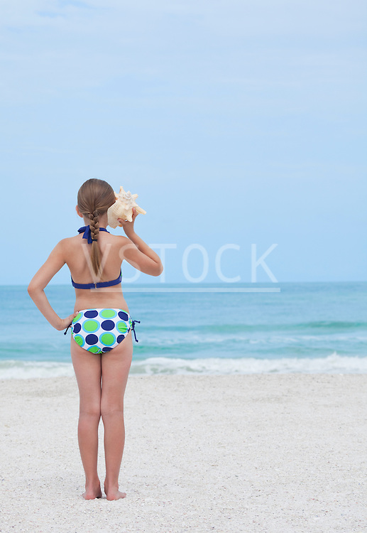 USA, Florida, St. Pete Beach, Rear view of girl (8-9) listening to conch shell on beach