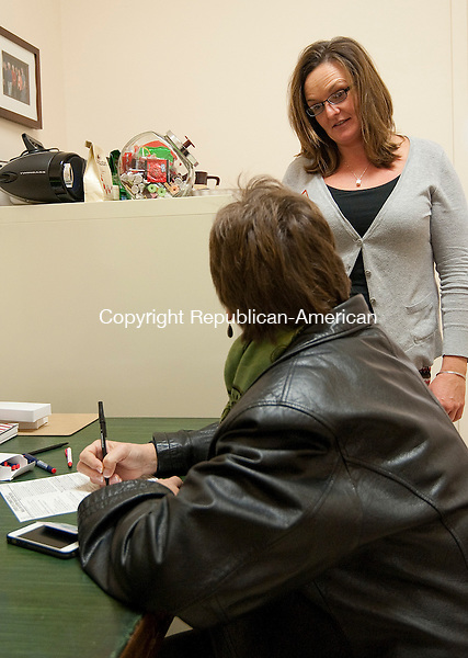 WINSTED, CT-110414JS06- Georgi Andrews, Assistant Registrar in Winsted, right, talks with Victoria Ford as Ford fills out a same-day voters registration form at Town Hall in Winsted on Tuesday. Ford thought she was registered, but when she showed up at Pearson School, she found out she was not. She said it was just an oversight on her part. <br /> Jim Shannon Republican-American