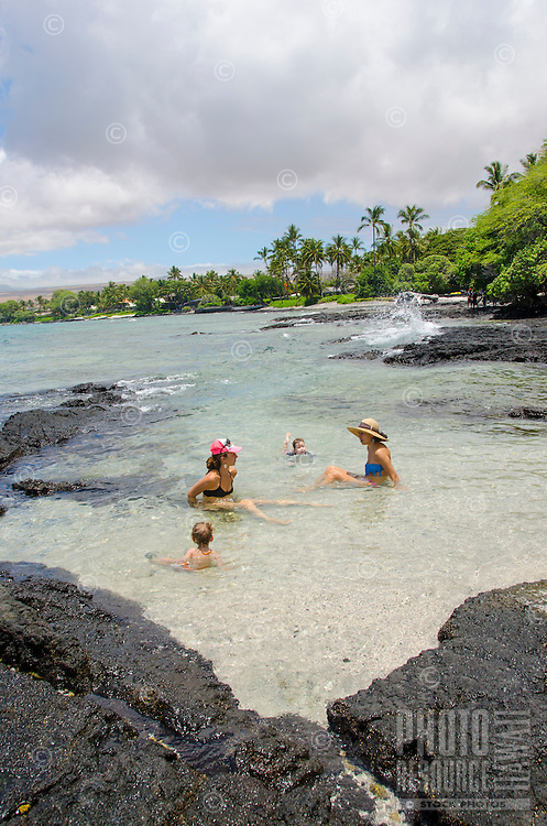 Two local children and their mothers enjoy a tidal pool at a beach in Puako on a sunny day, South Kohala, Big Island.