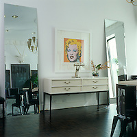 "A bright note of yellow is struck by an Andy Warhol ""Marilyn"" screenprint hanging between two full-length mirrors in the black-and-white dining room of this New York town house"
