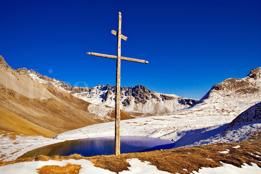 Wooden cross stands above the Lac de Souliers, a perfect tarn at 2490m, in a cirque of limestone mountains. Queyras, Hautes Alpes, Provence, France.